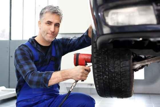 Serwis opon.Mechanik samochodowy dokręca kluczem pneumatycznym koła w samochodzie.