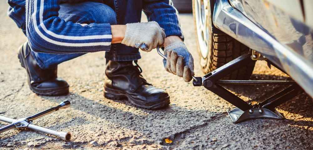 mechanik-podnosi-samochod-na-podnosniku