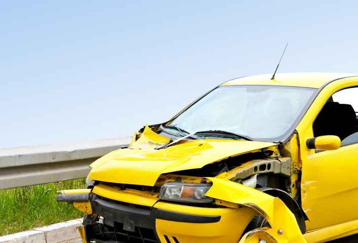 Front view of crashed yellow car at highway